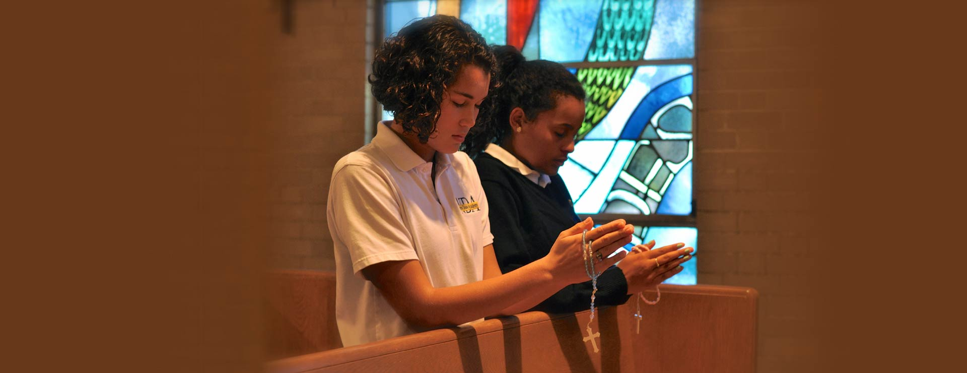 Two students praying the rosary in the chapel at the Notre Dame Academy catholic all girls school students praying in the campus chapel in Northern Kentucky.