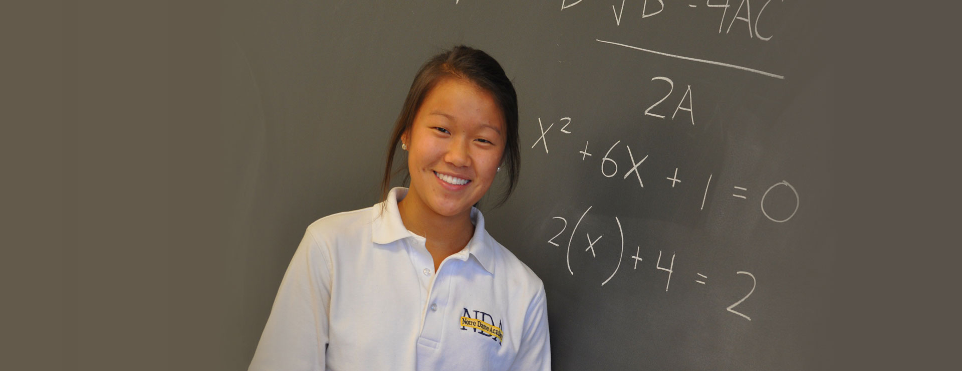 A student standing in front of a chalkboard containing a math equation Notre Dame Academy catholic all girls school students praying in the campus chapel in Northern Kentucky.