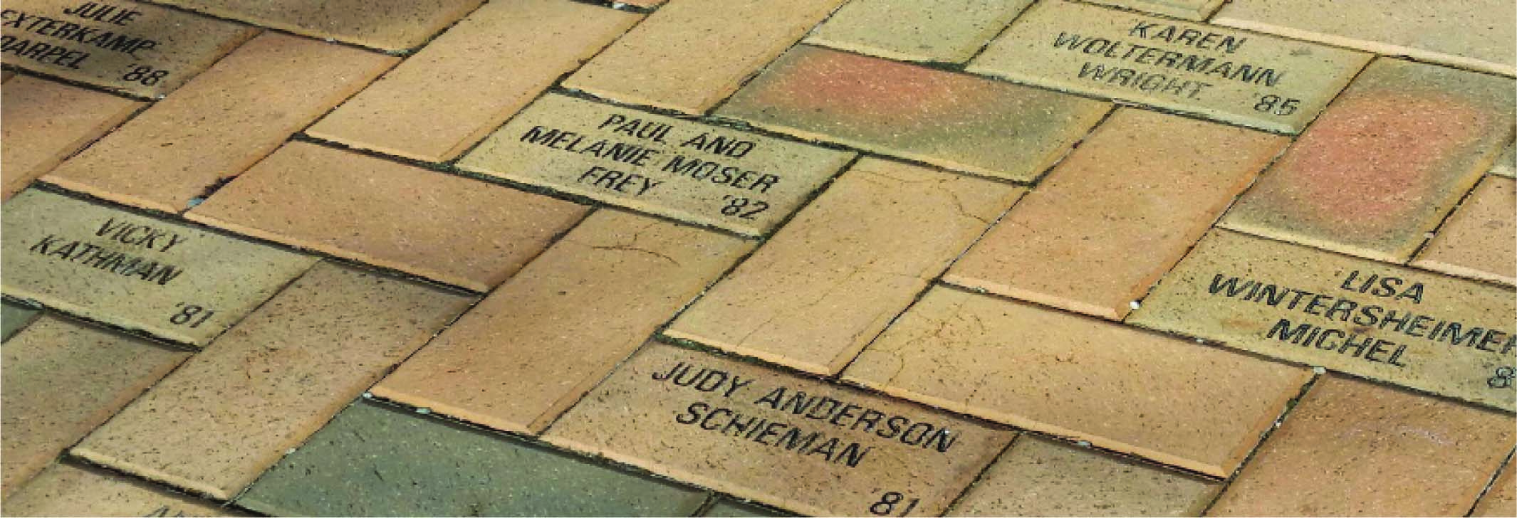 A close up of a brick walkway showing various commemorative bricks donated from different years.