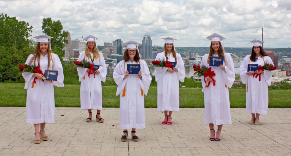 Students standing in a park overlooking the city in their graduation gowns holding their diplomas after graduating from the Notre Dame Academy catholic all-girls school in Covington, Northern Kentucky.