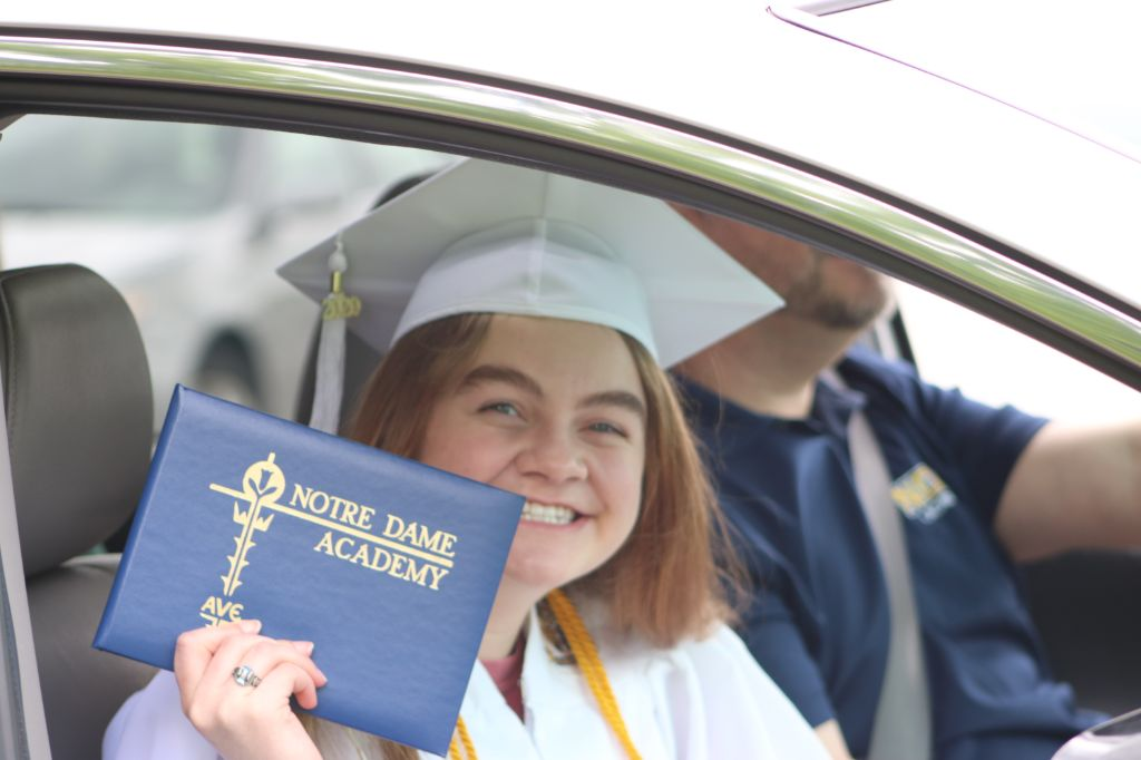A student sitting in their car holding their diploma and smiling at the camera at the Notre Dame Academy catholic all-girls school in Covington, Northern Kentucky.