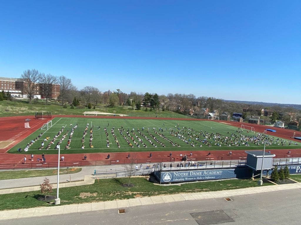 View of a prayer service taking place outside on one of the practice fields at the Notre Dame Academy catholic all-girls school in Covington, Northern Kentucky.