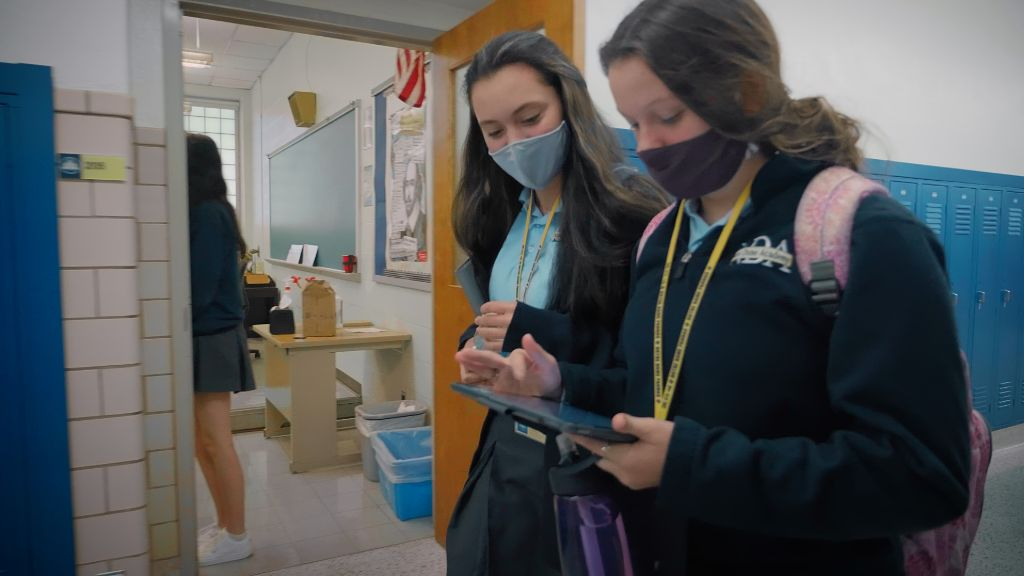Two students both looking over an iPad while standing in the hallway at the Notre Dame Academy catholic all-girls school in Covington, Northern Kentucky.