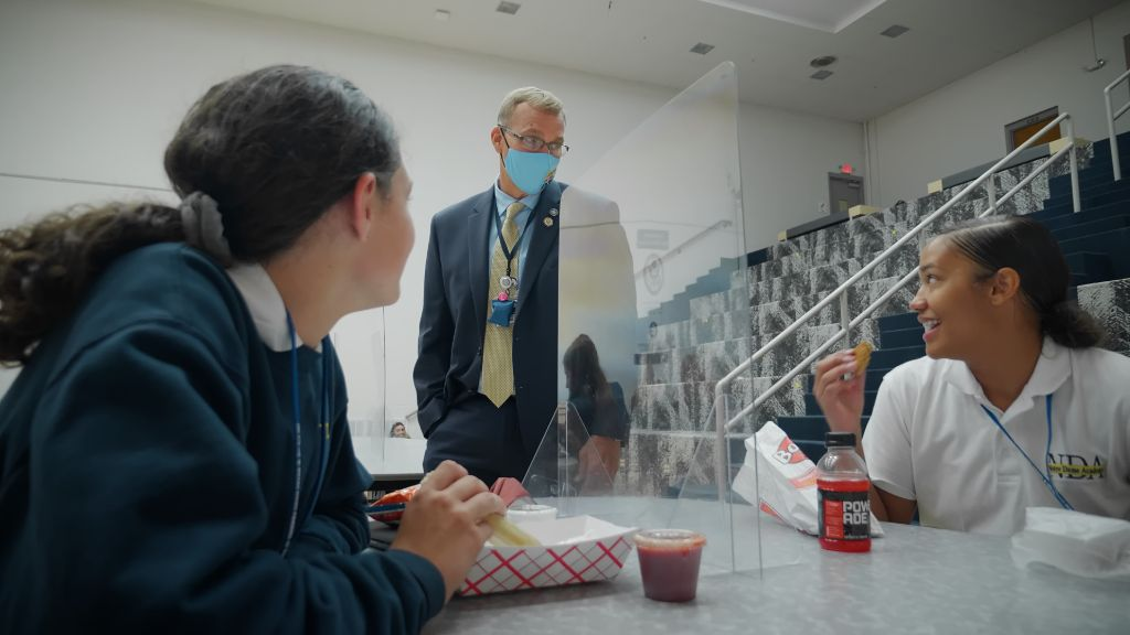 The Principal, Jack VonHandorf, stopping to say hi to students eating lunch in the cafeteria at the Notre Dame Academy catholic all-girls school in Covington, Northern Kentucky.