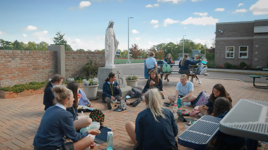 Students sitting outside eating lunch around the statue of the Virgin Mary at the main entrance to the school at the Notre Dame Academy catholic all-girls school in Covington, Northern Kentucky.