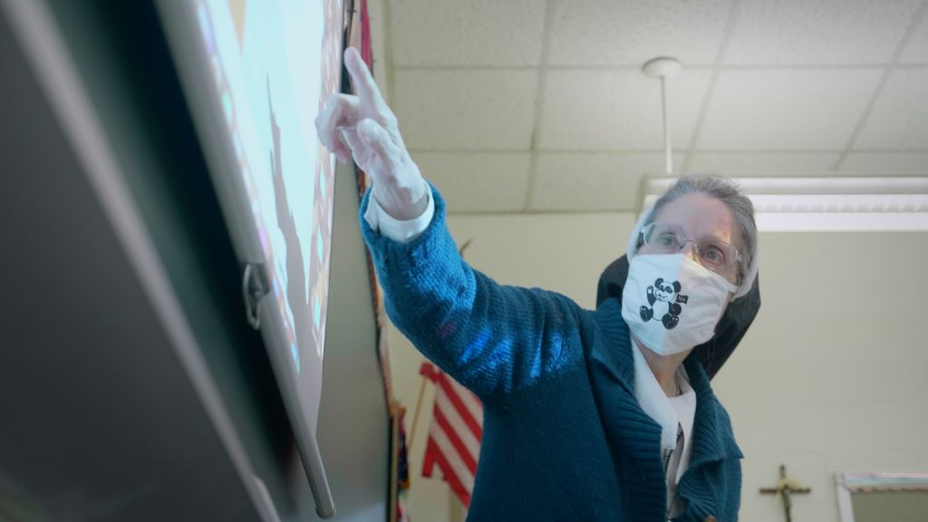 A teacher wearing a face mask leaning towards the white board pointing out information to her students at the Notre Dame Academy catholic all-girls school in Covington, Northern Kentucky.