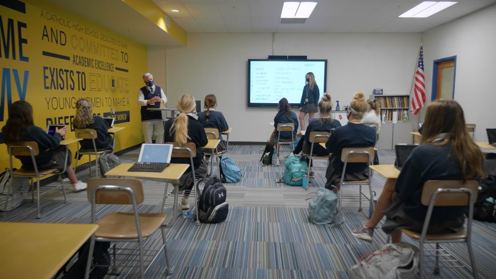 A view from the back of the classroom of students sitting socially distant wearing protective face masks while the teacher presents information at the Notre Dame Academy catholic all-girls school in Covington, Northern Kentucky.