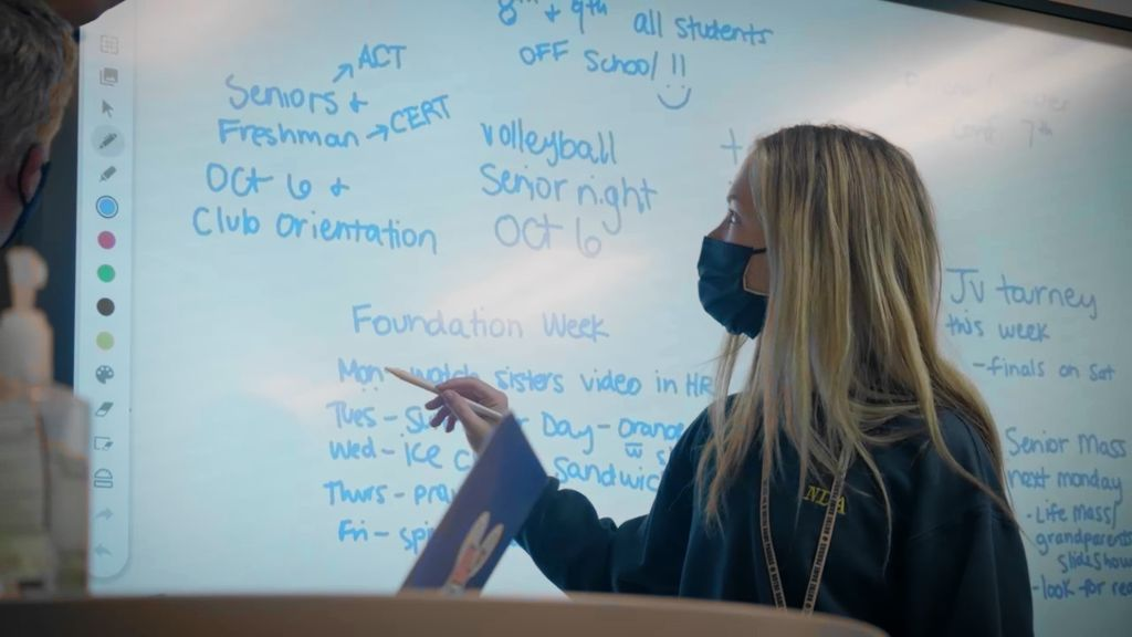 A student standing in front of a whiteboard pointing out information at the Notre Dame Academy catholic all-girls school in Covington, Northern Kentucky.