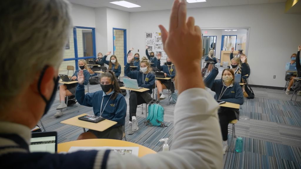 A view over a teacher's shoulder of the students in the classroom seated socially distant wearing protective face masks at the Notre Dame Academy catholic all-girls school in Covington, Northern Kentucky.