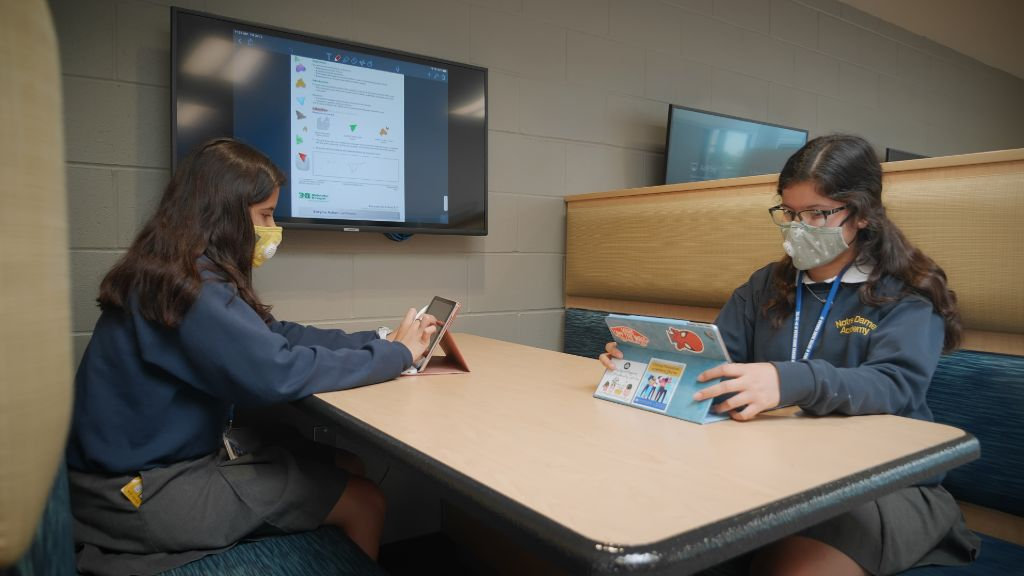 Two students sitting in a booth studying on their iPads at the Notre Dame Academy catholic all-girls school in Covington, Northern Kentucky.