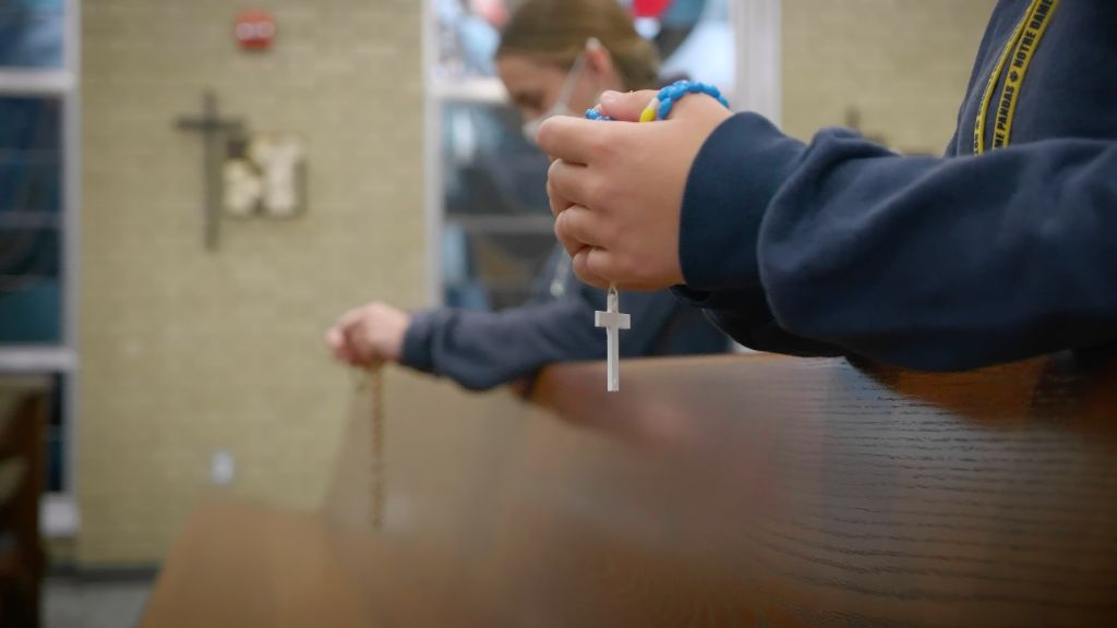 A view of students kneeling at the pews praying the rosary at the Notre Dame Academy catholic all-girls school in Covington, Northern Kentucky.