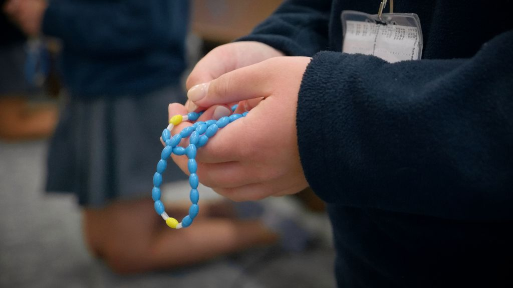 A close up of the hands of a student holding the rosary in prayer at the Notre Dame Academy catholic all-girls school in Covington, Northern Kentucky.