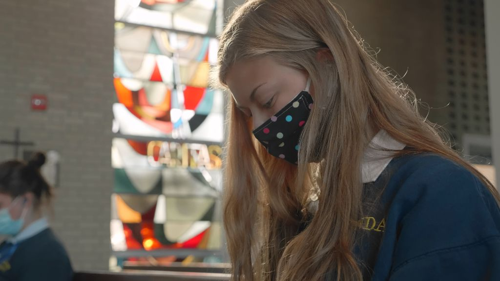 A closeup of a student with their eyes closed praying in the chapel at the Notre Dame Academy catholic all-girls school in Covington, Northern Kentucky.
