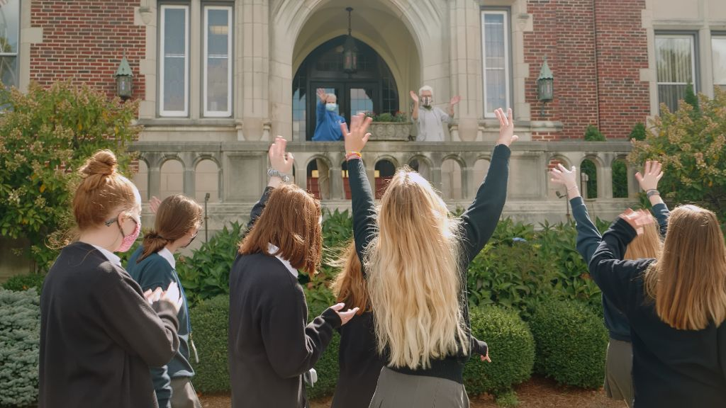 Students outside the school waving at teachers on the steps of the building at the Notre Dame Academy catholic all-girls school in Covington, Northern Kentucky.