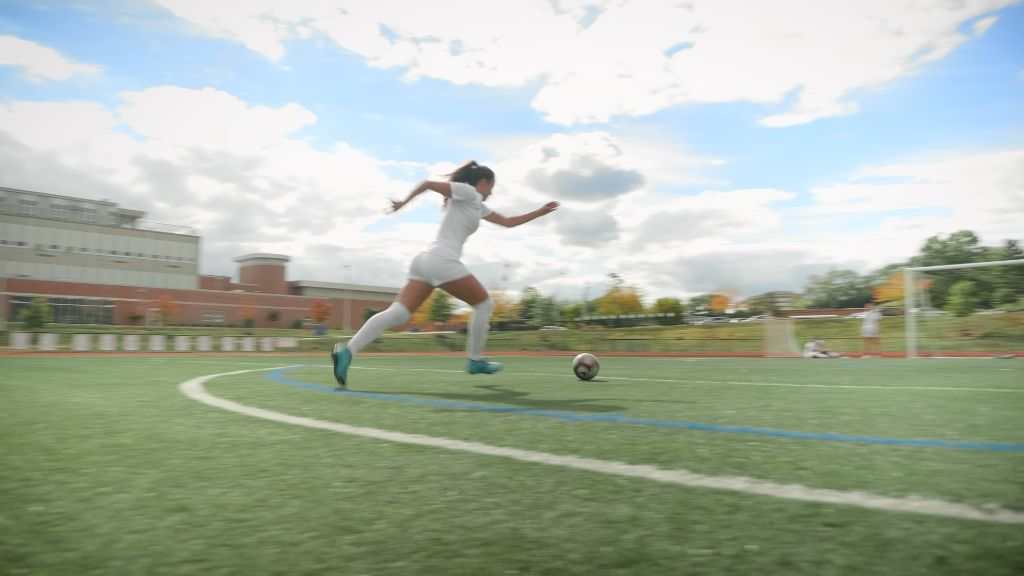 Student athlete soccer player sprinting across the field kicking a soccer ball at the Notre Dame Academy catholic all-girls school in Covington, Northern Kentucky.