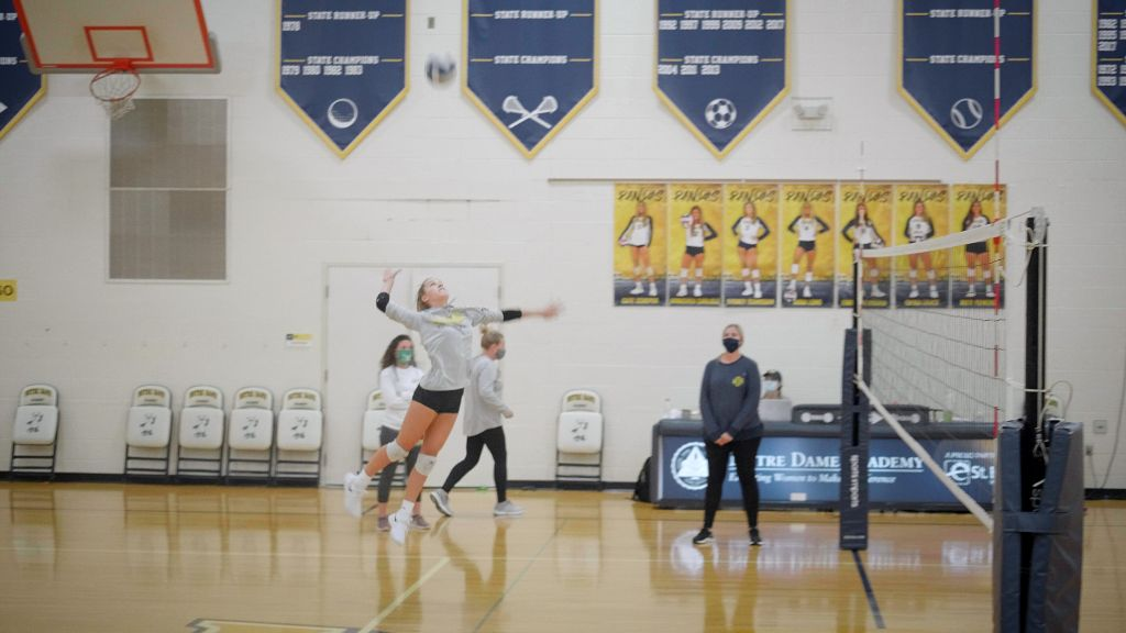 A student athlete jumping to spike a volleyball at the Notre Dame Academy catholic all-girls school in Covington, Northern Kentucky.