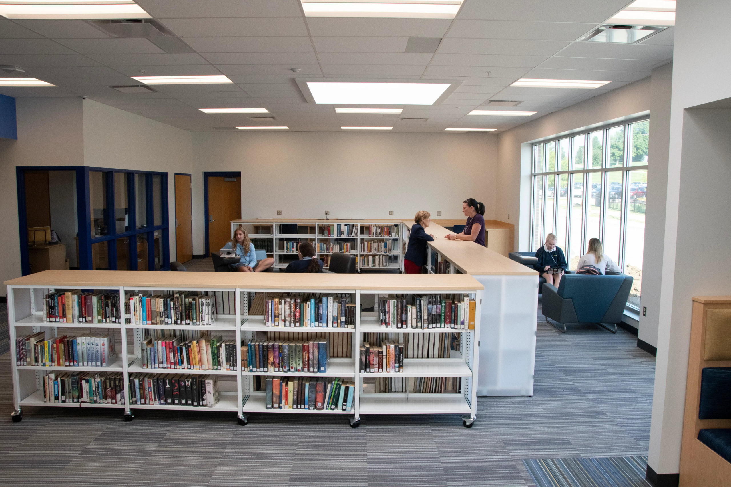 A view of the shelves filled with books and the students sitting and studying at chairs and tables in the Collaborative Learnin Center at Notre Dame Academy catholic all-girls school in Northern Kentucky.