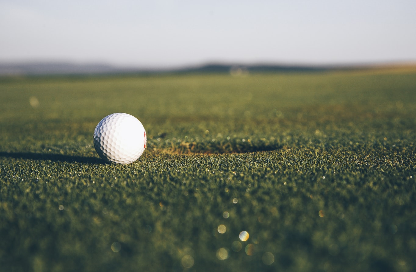 A golf ball rolling into a hole.